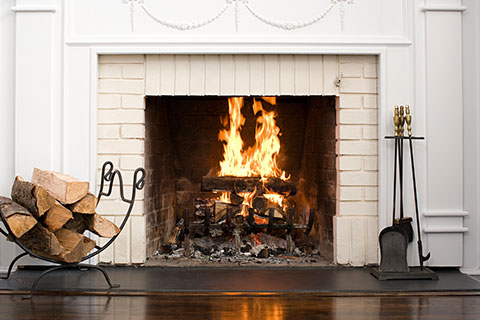 Home Inspector Keswick picute of a wood burning firplace with white brick border representing a fireplace that a home inspector would do a WETT inspection on